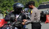 Seorang petugas kepolisian memeriksa surat kelengkapan pengendara sepeda motor di Taman Imbi, Jayapura, Papua, Senin (18/5/2020). Petugas gabungan mulai melakukan penyekatan 16 titik di Kota Jayapura, Papua guna membatasi aktivitas masayarakat untuk mencegah penyebaran COVID-19