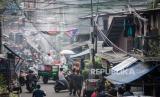 Petugas Palang Merah Indonesia (PMI) Jakarta Pusat menyemprotkan cairan disinfektan di pemukiman padat penduduk  di kawasan Kebon Melati, Jakarta, Sabtu (28/3). Penyemprotan yang dilakukan di tiga kelurahan diantaranya Kelurahan Kebon Melati, Kelurahan Petamburan, Kelurahan Kebon Kacang sebagai upaya mengantisipasi penyebaran virus corona COVID-19 di area tersebut.