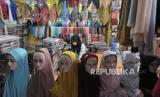 Pedagang menunggu pembeli di toko miliknya di pusat kain dan busana muslim