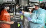 Sejumlah petugas  paramedis mengenakan pakaian pelindung saat bersiap untuk bekerja di rumah sakit lapangan sementara yang didirikan di Ifema convention and exhibition centre, Madrid, Spanyol, Selasa (31/3). Setelah menghadapi hari ke-17 masa lockdown, pemerintah Spanyol memperketat aturan lockdown serta menghentikan sementara semua pekerjaan konstruksi dan kegiatan ekonomi serta wajib mengisolasi diri dirumah bagi warganya sebagai upaya pencegahan penyakit pandemi COVID-19