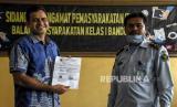 Mantan terpidana kasus korupsi Wisma Atlet Muhammad Nazaruddin (kiri) bersama Pembimbing Kemasyarakatan Madya Balai Pemasyarakatan (Bapas) Bandung Budiana (kanan) menunjukkan surat bebas murni di Balai Pemasyarakatan (Bapas) Kelas I Bandung, Jalan Ibrahim Adjie, Kota Bandung, Kamis (13/8). Mantan Bendahara Umum (Bendum) Partai Demokrat tersebut resmi bebas murni hari ini, Kamis (13/8), setelah dua bulan menjalani masa cuti menjelang bebas di Balai Pemasyarakatan (Bapas) Kelas I Bandung. Foto: Abdan Syakura/Republika