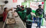 Sejumlah driver ojek online mengantre menunggu layanan makanan gratis di salah satu warteg di kawasan Palmerah, Jakarta  Barat, Selasa (7/4). Ojek online adalah salah satu sektor yang terdampak penerapan Pembatasan Sosial Berskala Besar (PSBB).