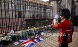 Seorang pria dengan pakaian Queens Guard di depan Istana Buckingham setelah kerajaan mengumkan berita duka cita atas meninggalnya Pangeran Philip, London, Inggris, Jumat (9/4).