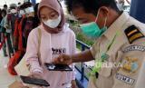 Petugas memindai kode batang surat kesehatan milik penumpang kapal dari Kepulauan Riau yang melakukan perjalanan mudik lebih awal di Pelabuhan Bandar Sri Junjungan Dumai, Riau, Kamis (22/4/2021). Aktivitas pelabuhan penumpang di Dumai mulai ramai disinggahi pemudik dari Kepulauan Riau untuk menghindar dari pemberlakuan larangan mobilitas mudik Idul Fitri 1442 H/2021 M terhadap Pelaku Perjalanan Dalam Negeri (PPDN) yang berlaku selama H-14 pada 22 April hingga 5 Mei 2021 dan H+7 pada 18 Mei sampai dengan 24 Mei 2021.