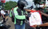 Pengemudi ojek daring menerima bantuan sembako dari Presiden Joko Widodo di Terminal Baranangsiang, Kota Bogor, Jawa Barat, Kamis (9/4/2020). Sebanyak 500 paket sembako dibagikan untuk warga yang terkena dampak ekonomi akibat wabah pandemi virus Corona (COVID-19) di Kota Bogor