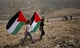 Dua anak membawa bendera Palestina.