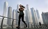 Seorang wanita lari pagi di depan gedung pencakar langit di kawasan Marina Dubai.  (AP/Kamran Jebreili)