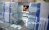 Petugas menata tumpukan uang di cash pooling salah satu bank di Jakarta. LPS mencatat pertumbuhan tabungan Rp 500 juta melambat.