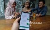 Sejumlah anak muda tengah membuka rekening Mandiri Syariah melalui aplikasi Mandiri Syariah Mobile di salah satu kafe di Jakarta, Rabu (8/1).