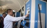 Petugas membatu pengemudi taxi melakukan pengisian daya pada mobil listrik di Stasiun Pengisian Kendaraan Listrik Umum (SPKLU) PLN di Kantor PLN Disjaya, Gambir, Jakarta, Selasa (28/1).