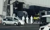 Petugas mengenakan pakaian pelindung berada di sekitar pesawat yang mendarat membawa warga Jepang dari Wuhan di Bandara Haneda, Tokyo, Jepang, Rabu (29/1). Sejumlah maskapai menangguhkan penerbangan ke sejumlah kota di China.