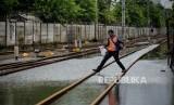 Petugas berjalan di perlintasan rel KRL yang terendam banjir. Rekayasa KRL berlanjut karena sebagai stasiun di DKI Jakarta masih terendam banjir