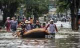 Petugas mengevakuasi warga menggunakan perahu karet saat terjadi banjir di kawasan Bendungan Hilir, Jakarta, Selasa (25/2).