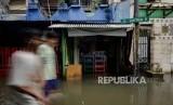 Warga berjalan melintasi area yang terendam banjir di Jalan Satria IV, Kelurahan Jelambar, Jakarta Barat, Selasa (25/2).