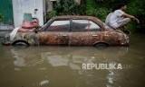 Warga menghindari genangan air di Jalan Satria IV, Kelurahan Jelambar, Jakarta Barat, Selasa (25/2).