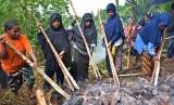 Sejumlah mama muslim Wamena memilih batu panas yang akan diletakkan ke lobang bakar batu di Kampung Meteo, Kota Jayapura, Papua, Ahad (5/6). (Antara/Indrayadi TH)