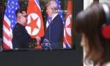 Seorang pria menonton layar TV yang menyiarkan pertemuan  Presiden AS Donald Trump dengan pemimpin Korea Utara Kim Jong Un di Seoul Railway Station di Seoul, Korea Selatan, Selasa (12/6).