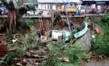 Petugas Dinas Lingkungan Hidup (DLHK) Pemkot Depok mengevakuasi sisa barang dari warung yang terbawa longsor di sisi jalan Raya Citayam-Depok, Jawa Barat, Jumat (9/11/2018).