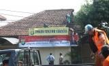 Petugas kepolisian memperbaiki kantor Polsek bekas perusakan dan pembakaran di Polsek Ciracas, di Jakarta, Kamis (13/12/2018).