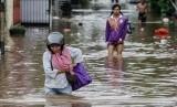Warga melintasi banjir. (Ilustrasi)
