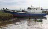 Dua nelayan mendayung sampannya di dekat KM Nelayan 2016 - 13 bantuan dari Kementerian Kelautan dan Perikanan yang rusak di Teluk Kendari, Kendari, Sulawesi Tenggara, Senin (4/2/2019).