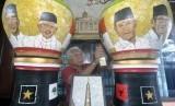 Seniman Bambang Sriyanto (69 tahun) menyelesaikan pembuatan lukisan limbah cangkang telur bertema Pemilihan Presiden 2019 melalui media guci di rumahnya di Perumnas Bantarjati, Kota Bogor, Jawa Barat, Selasa (12/3/2019).