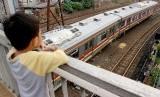 Seorang bocah mengamati rangkaian kereta rel listrik (KRL) Commuterline melintas di kawasan Stasiun Jatinegara, Jakarta, Selasa (9/4/2019).
