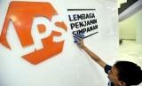 Karyawan membersihkan logo baru Lembaga Penjamin Simpanan (LPS) di Jakarta, Selasa (23/4/2019).