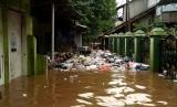 Seorang warga berusaha membersihkan sampah yang terbawa aliran banjir di kawasan permukiman penduduk Cililitan Kecil, Jakarta, Jumat (26/4/2019).
