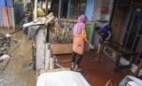 Warga membersihkan rumah dan harta bendanya pascabanjir merendam kawasan Kelurahan Rawajati di Jakarta, Senin (29/4/2019).