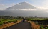 Pengendara melintasi Kayu Aro Barat dengan latar Gunung Kerinci, Jambi, Jumat (3/5/2019).