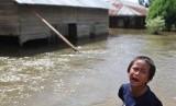 Seorang anak menangis di depan rumahnya yang terendam banjir di Desa Laikandonga, Konawe Selatan, Sulawesi Tenggara, Senin (17/6/2019).