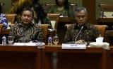 Ketua Dewan Komisioner Otoritas Jasa Keuangan (OJK) Wimboh Santoso (kanan) mengikuti rapat kerja bersama Komisi XI DPR di Kompleks Parlemen, Senayan, Jakarta, Kamis (27/6/2019).