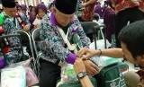 Petugas sedang memasangkan gelang identitas pada salah seorang Jamaah Calon Haji Kloter 1 dari Kabupaten Bogor di Asrama Haji Embarkasi Jakarta-Bekasi, Kota Bekasi, Sabtu (6/7).