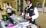 Petugas Perlindungan Jamaah (Linjam) Eva Widiastuti, menunjukkan sejumlah barang yang disita dari jamaah haji asal Embarkasi Surabaya, Jumat (12/7). Barang-barang yang disita antara lain, rokok, jamu kuat, sari rapet, dan lainnya.