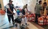 Seorang petugas membantu jamaah yang menggunakan  kursi roda saat tiba di pemondokan di Madinah, Rabu (17/7)  pagi waktu Arab Saudi. Rata-rata sekitar 20-25 jamaah dalam setiap kloter menggunakan kursi roda.