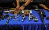 Petugas Kepolisian Polda Riau memperlihatkan barang bukti senjata api saat konferensi pers terkait penggrebekan tempat tinggal buronan yang menjadi gembong narkoba di Mapolda Riau, di Pekanbaru, Riau, Selasa (23/7/2019).