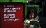 Seorang bocah membaca buku yang dipinjamkan secara gratis. Ilustrasi