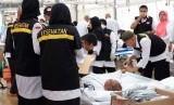 Petugas memberikan perawatan kepada jamaah haji Indonesia yang sebagian besar akibat kelelahan dan dehidrasi di Posko Kesehatan Mekkah, Arab Saudi, Minggu (11/8/2019).