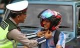 K'Mutrans II untuk mengedukasi tertib lalu lintas di kalangan remaja melalui lagu. FotoPolantas membantu mengencangkan tali helm pengendara sepeda motor saat dilakukan kampanye