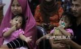 Bayi kembar siam Aqila (kiri) digendong ibunya Silvina Dewi dan Azila (kanan) digendong bapaknya Jayasri saat acara syukuran atas keberhasilan pemisahan bayi kembar siam asal Kendari, Sulawesi Tenggara, di Rumah Sakit Umum Daerah (RSUD) Dr Soetomo, Surabaya, Jawa Timur, Jumat (20/9/2019).