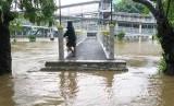 Warga berada di atas jembatan Sungai Ciliwung yang meluap di kawasan Pasar Baru, Jakarta Pusat (ilustrasi).