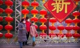 Sejumlah warga mengenakan masker berjalan melewati hiasan perayaan tahun baru Imlek yang dibatalkan di Taman Longtan di Beijing, Sabtu, (25/1/2020). Penyebaran virus corona di China membuat WNI diimbau KBRI Beijing untuk pulang ke Tanah Air.