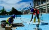 Pekerja menyelesaikan pembangunan venue Aquatic PON XX Papua di Kampung Harapan, Sentani, Jayapura, Papua, Kamis (30/1/2020).
