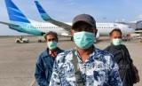 Penumpang maskapai lokal menggunakan masker saat akan menaiki pesawat. Ditutupnya jalur penerbangan ke China membuat pemerintah berencana memberikan insentif ke maskapai.
