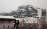 Pengunjung berjalan melewati kapal pesiar Diamond Princess yang dikarantina pada hari Ahad, (16/2), di Yokohama, dekat Tokyo.