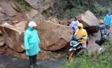Batu besar sisa material longsoran menutup akses jalan di Kecamatan Cikajang, Kabupaten Garut, Selasa (25/2) sore.