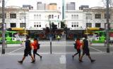 Pejalan kaki bermasker melintas di psat bisnis Melbourne, Australia, Rabu (22/7). Pemerintah Australia melaporkan rekor baru kasus Covid-19 di Victoria dan memicu kekhawatiran gelombang kedua.