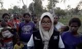 Ahli gizi kesehatan masyarakat yang menjadi relawan ACT, Harum Aulia Rahmawati bersama warga Asmat, Papua