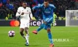 Alex Sandro melepas tembakan ke gawang Lyon dikawal Karl Toko Ekambi, pada leg pertama babak 16 besar Liga Champions antara Lyon dan Juventus di Lyon, Perancis.